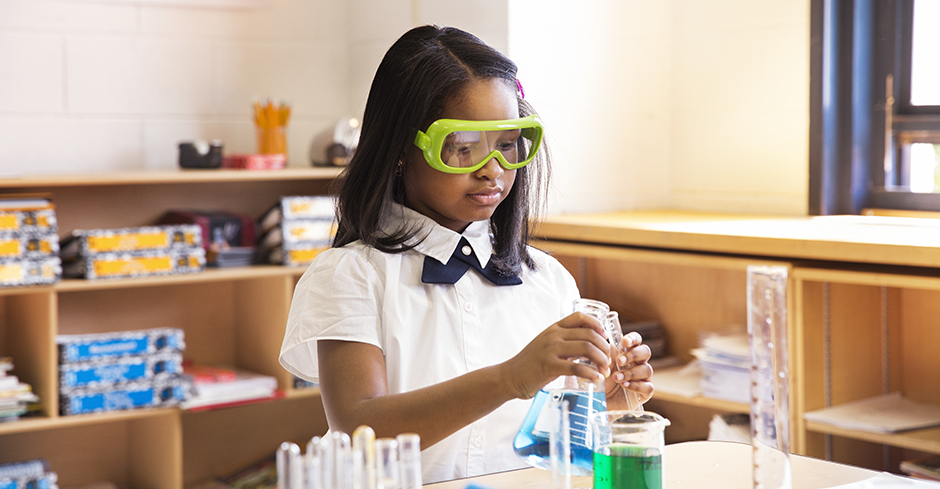 African American girl conducts science experiment in classroom