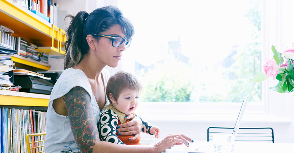 Tatooed woman holds her infant while doing laptop work in an office